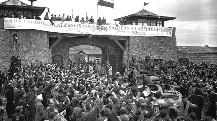 Prisioneros de Mauthausen saludan a la 11ª División Acorazada de los EE UU por su liberación bajo una pancarta escrita en español.