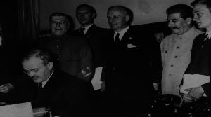 El Ministro de Asuntos Exteriores Soviético Vyacheslav Molotov firmando el pacto de no agresión entre la URSS y la Alemania nazi. Junto a el el Ministro de Asuntos Exteriores alemán Joachim von Ribbentrop y Josef Stalin.